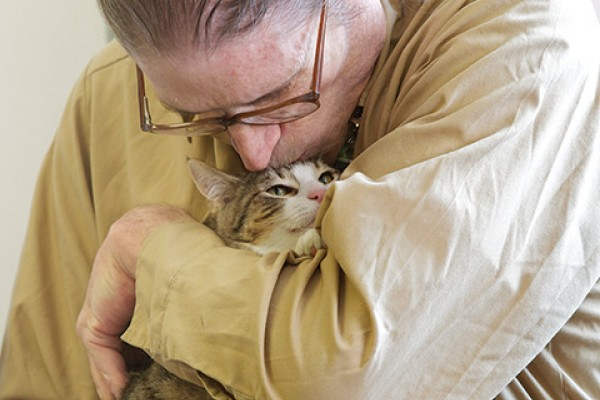 Foster cat Amaryllis snuggles up to Monroe Correctional Complex inmate Gary Grant during a party celebrating the 500th cat to go through the fostering program that prisoners run in conjunction with Purrfect Pals cat sanctuary.